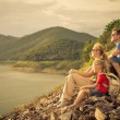 Happy family sitting near the lake at the day time. — Stock Photo #53742451
