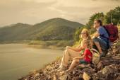 Happy family sitting near the lake at the day time. — Stock Photo