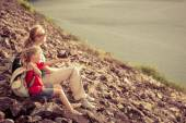Mother and daughter sitting near the lake at the day time. — Stock Photo