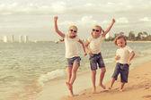 Three happy children dancing on the beach — Stock Photo
