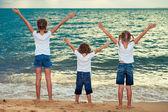 Three happy children standing on the beach — Stock Photo