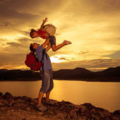 Father and daughter playing on the coast of lake at the sunset t — Stock Photo