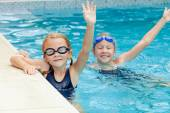 Two happy little girls playing  in the swimming pool — Stock Photo