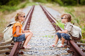Two little kids with backpack sitting on the railway — Stock Photo