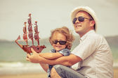 Father and son playing on the beach at the day time. — Stock Photo