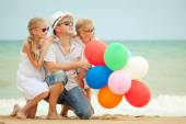 Happy family sitting on the beach at the day time. — Stock Photo