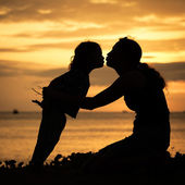 Mother and son playing on the beach at the sunset time. — Stock Photo