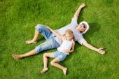 Portrait a father and daughter lying on the grass at the day tim — Stock Photo