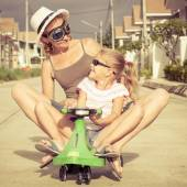 Mother and little daughter playing near a house at the day time. — Stock Photo