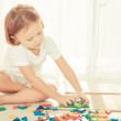 Little boy playing with wooden mosaic on the floor — Stock Photo #55491913