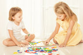 Two kids playing with wooden mosaic in their room on the floor — Stock Photo