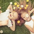 Happy little boy and girl lying on the grass — Stock Photo #55774957