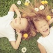 Happy little boy and girl lying on the grass — Stock Photo #55774965