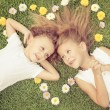 Happy little boy and girl lying on the grass — Stock Photo #55775467