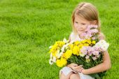 One happy little girl sitting on the grass with a bouquet of flo — Stock Photo