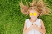 En glad liten flicka liggande i gräset — Stockfoto