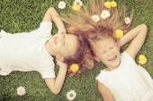 Happy little boy and girl lying on the grass — Stock Photo