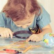 Little boy considering a world map with a magnifying glass — Stock Photo #56392777