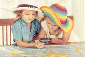 Brother and sister are considering a world map with a magnifying — Stok fotoğraf
