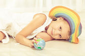 Little girl looking at a small globe — Stock Photo