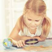 Little girl considering a world map with a magnifying glass — Stok fotoğraf