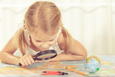 Little girl considering a world map with a magnifying glass — Stock Photo