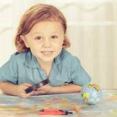 Little boy considering a world map with a magnifying glass — Stok fotoğraf
