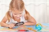 Little girl considering a world map with a magnifying glass — Стоковое фото