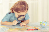 Little boy considering a world map with a magnifying glass — ストック写真