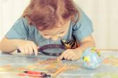 Little boy considering a world map with a magnifying glass — Стоковое фото