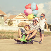Father and children playing near a house at the day time — Stock Photo
