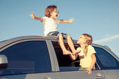 Happy brother and sister are sitting in the car — Stock Photo