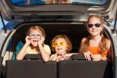 Happy brother and his two sisters are sitting in the car — Stockfoto