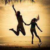 Mother and  daughter jumping on the beach — Stock Photo