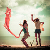 Two happy children jumping on the beach — Stock Photo