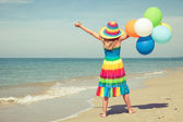 Little girl with balloons standing on the beach — Stock Photo