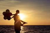Father and daughter with balloons playing on the beach at the da — Stock Photo