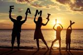 Happy family standing on the beach at the sunset time. — Stock Photo