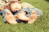 Father and son sitting on the grass at the day time. — Stock Photo
