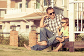 Father and son playing near the house at the day time. — Stock Photo