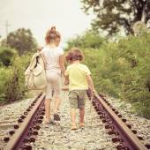 Two little kids with backpack standing on the railway — Stock Photo