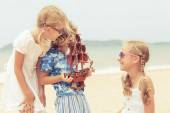 Two sisters and brother playing on the beach — Stock Photo