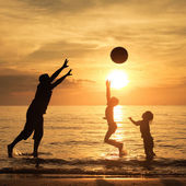 Father and children playing on the beach at the sunset time. — Stock Photo
