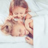 Lovely brother and sister lying in bed at home. — Stock Photo