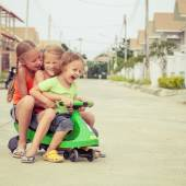 Three happy children playing on the road — Fotografia Stock