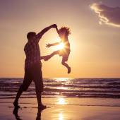 Father and son playing on the beach at the sunset time. — Stock Photo