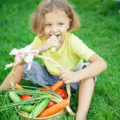 Happy little boy sitting on the grass with a basket of vegetable — Stok fotoğraf