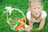Happy little girl lying on the grass with a basket of vegetables — Stock Photo