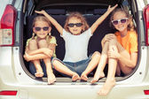 Happy brother and his two sisters are sitting in the car — Stock Photo