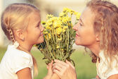 Mother and daughter playing on the grass at the day time. — Stock Photo
